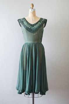 1940s hunter green sheer beaded party dress. Vintage 40s dress features gathered v-neckline with floral applique and silver beading. The waistline has shirring that flows out to a full flared skirt with slight asymmetrical hemline adorned with ruffles.