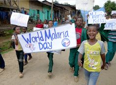 Participants in the World Malaria Day march from the upper heights of Bonga, Ethiopia, to its low, malaria-prone valley carrying signs raising awareness of malaria and malaria prevention.