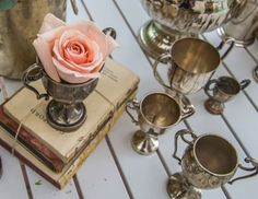 Vintage bookstack with some baby metal trophies from our odds and sods collection Ancient Greece, Silk Flowers, Backdrops, Tea Cups, Wedding Decorations, Table Settings, Metal, Tableware, Baby