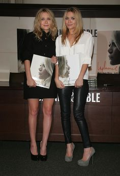 Twinning combo: For a 2008 NYC book signing, both girls proved neutral separates can be just as stylish as their printed and textured counterparts. Mary-Kate went monochromatic in a black shirtdress and patent pumps. Ashley accessorized her soft white blouse with black leather pants and gray suede pumps.