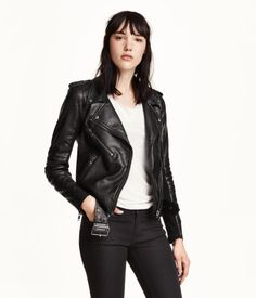 Biker jacket in black with shoulder tabs, lapels with snap fastener, & diagonal zip at front. Features quilted sleeves, a chest pocket, side pockets with zip, & a removable belt. | H&M Divided