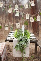 Weddind table setting with white plates and green glasses decorated with white candles, green leaves and eucalyptus and a garland of green leaves and postcards outdoors