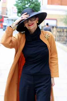 Svelte in black. LOVE the hat. The muted orange, gold (esp. the brooch), and red lipstick make it feel autumnal but not at all Halloween.