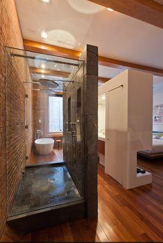 baño integrado en dormitorio, mueble para lavabo como separación, cabina de ducha con acabado de piedra, suelo de parquet