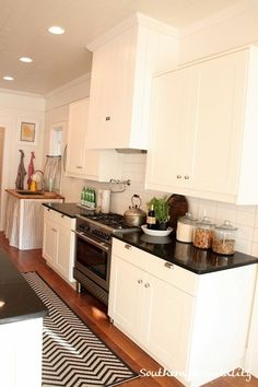 source: Southern Hospitality  Southern Living Idea House - Fantastic kitchen with Ikea kitchen cabinets paired with Absolute Black Granite countertops. White wood paneled ceiling with pot lighting. Warm brown kitchen hardwood floors with Ballard Designs Chevron Stripe Indoor/Outdoor Rug. Skirted sink with butcher block top and stripe cafe curtains.