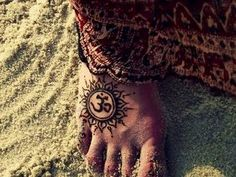 Foot tattoo of sun and ohm
