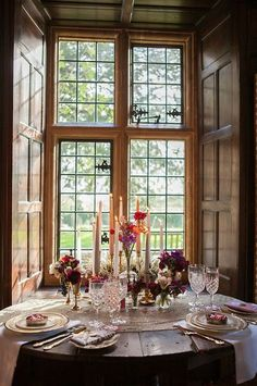 A view of dinner table and a window with a view of the house across the street