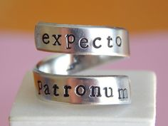 Wonderful twist aluminum ring handstamped with the words EXPECTO PATRONUM Magic Book Inspired  If you prefer your own quote, just let us know then well stamp what you want at no additional cost.  Stamping done by hand each letter, name or design may have slight variations in alignment, spacing and depth. Each piece will not look alike, each piece is unique with detail.  PURE 1100 ALUMINIUM It is FOOD SAFE and safe on your skin. There are less skin reactions with FOOD SAFE ALUMINUM, than with…