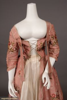PINK SILK BROCADE ROBE A LA FRANCAISE, 1770-1780. Sack back open gown of rose pink ribbed silk brocaded with scattered multicolored flower sprays and small cream flower sprigs, looped cream silk fringe trim, bodice with pendant self fabric bands to cross-over and pin under arms, center front eyelets forlacing, skirt knife pleated to bodice, interior linen waist tapes and loops for polonaise effect, homespun linen bodice and sleeve linings, hem deeply faced with soft cream China silk. Detail