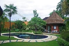 Tropical planted backyard paradise with a pool. This pool has a really cool idea for the step stone path that goes around it. This is a great way to separate the pool from the lawn and rest of the landscape without using a whole lot of concrete.