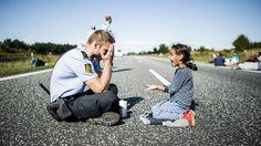 LEK I ALVORET: Den lille syriske jenta og den danske politimannen leker på den stengte motorveien onsdag.FOTO: MICHAEL DROST-HANSEN / JYLLANDS-POSTEN/ POLFOTO