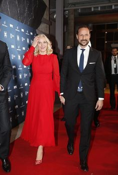 Crown Princess Mette-Marit of Norway in an elegant scarlet floor-length dress with a pair of eye-catching lace stilettos by British Designer Nicholas Kirkwood. Adding a touch of glamour to her ensemble for a pair of diamond encrusted statement earrings. Meanwhile, Crown Prince Haakon of Norway, cut a dapper figure in a navy two-piece suit and a trendy skinny tie as they attend the Sport Gala Awards 2018 in Hamar, Norway.