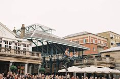 The market: The Piazza in Covent Garden, London. Tourists, shoppers, meanderers, performers, passers-by, lovers, and friends crowd together in the neighborhood's famous square.