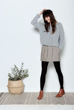 With gray sweater, printed skirt and black tights