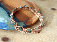 Green Holly Bracelet with Chinese Jade Stone Beads on Woven Leather with a Copper Clasp.