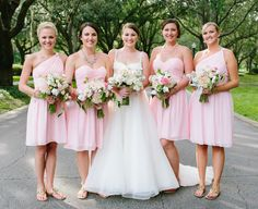 The bride and bridesmaids in pink ready for the ceremony by the lake.