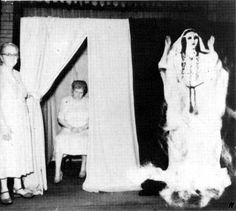 """Ethel Post Parrish sits in The Spirit Cabinet or """" Ghost Booth"""" producing ectoplasm to materialize the entity Silver Belle during a seance under test conditions in the United States, 1953."""