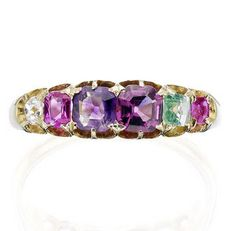 A gem-set 'Regard' ring Set with a graduated row of cushion-cut gems - ruby, emerald, garnet, amethyst, ruby and diamond, spelling 'REGARD', all to claw settings, between scalloped shoulders to a plain hoop, inscribed 'J. McK' inside shank.