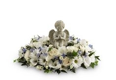 The Little Angel™ Ring of Flowers by FTD® - Ray Hunter Florist & Garden. A stone cast cherub statue sits in the center of a ring of white roses, white traditional daisies, white monte casino asters, light blue delphinium, white gladiolus and a variety of lush greens to create a beautiful tribute that expresses your unending love and affection for the deceased.Flowers and statute may vary due to seasonal availability.