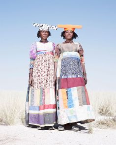 Africa | Portrait of two Herero women wearing beautiful patchwork dresses Namibia | Conflict and Costume in Namibia by Jim Naughten