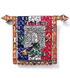 An Art Deco 'Arc de Triomphe Flag' brooch, by Cartier Paris, circa 1919. Set with round old- and rose-cut diamonds, faceted calibré rubies, sapphires, jacinths, fancy-cut faceted emeralds and faceted onyx, mounted in platinum and gold. 4.01 x 2.09cm. Cartier Collection. Source: Cartier 1899-1949, The Journey of a Style.