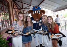 """First Year students pose for a photo with Durham Bulls Baseball Club mascot, Wool E. Bull, at the American Tobacco Campus during an orientation week event: """"A Night on the Town."""" After dinner, the students headed to the Durham Performing Arts Center for an evening of entertainment. © Duke Photography"""