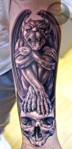 Gargoyle sitting on skull forearm tattoo