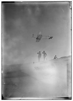 Side view from below of Orville Wright soaring in level flight, spectators looking up at glider; Kitty Hawk, North Carolina. 1911