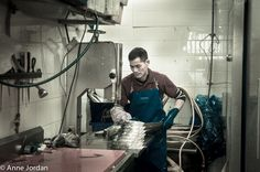 Cutting a large fish into fish steaks with an electric saw.