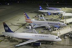 An American flight arrives at US Airways gate B6 during American Airlines' overnight move from Terminal 3 to Terminal 4 Tuesday, Feb. 25, 20...