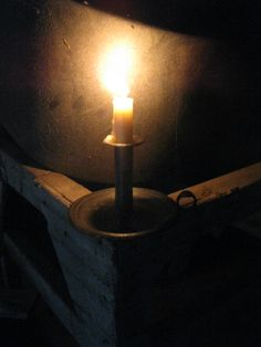 The lighted candle against the stone wall in the barn of HighButtonShoe.