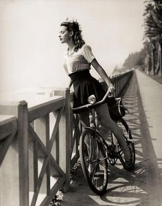 Vintage photo of a girl on a bicycle. Cute outfit!