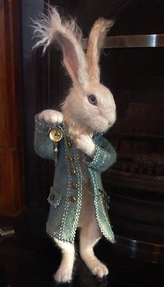 Needle felted White Rabbit by Paula Drage This is my version of Alice in wonderland's White Rabbit. He is needle felted with a Merino wool core and a mulberry silk overlay. I have made his coat by wet felting the wool and he holds a working pocket watch. He's 22 inch tall from the tips of his ears to his feet. Overall i'm quite pleased with the way he's turned out.