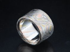 Bold, wide flat etched ring 12mm wide in mokume of 18K yellow gold, 14K palladium white gold, 14K red gold and sterling silver in tight woodgrain pattern.