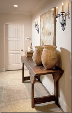 vignette for dining room.  console table plus rustic pottery and two candelabra sconces...  this would might make the from feel less formal?