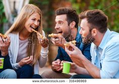 Pizza lovers. Group of playful young people eating pizza while having fun together - stock photo