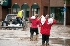 Residents carrying sandbags wade through floodwater in High River.Photograph: Mike Sturk/Reuters