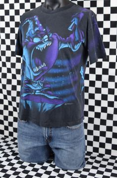 Fantastic Taz Wizard 2-sided 90s t-shirt! This print is awesome!  Condition: Good vintage condition with normal fading, a few spots and a tiny pin hole! Check out the close up pictures!  Tag: Looney Tunes  Era: 90s  Fabric: 100% Cotton **Vintage tshirt sizes may be different than contemporary shirt sizes so please check the measurements.**  Size: Large  Chest (pit to pit): 22  Length (top of the shoulder to bottom hem on front): 26  Vintage tshirts are usually 15-30 years or older and may…