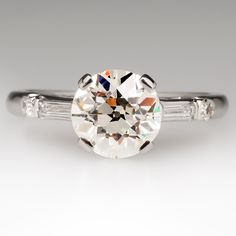 OMG Gorgeous, simply gorgeous - magnificent ring is one of our favorites. Stunning 2.03 carat old European cut center diamond w/lovely tapered baguette diamond accents & a single cut round diamond to cap off each side.