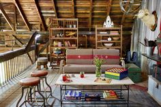 """Overhead, in the hay loft, an intimate seating arrangement provides a cozy spot for conversation. The vintage rattan settee boasts old military blankets-turned-cushions, while a """"wall"""" of vintage factory racks provides a lot of display space."""