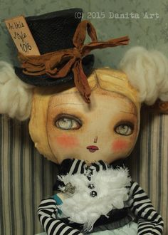 Alice In wonderland is celebrating an amazing anniversary this year, and I am celebrating too with new dolls with the Alice in Wonderland theme! This is Alice in Wonderland, borrowing the mad hatter's trademark top hat as she get ready to go to a tea party. This amazingly detailed doll measures 14 inches, hand made by me, Danita Art with patterns and clothes of my own design and confection. Alice wears a hand made dress with a soft blue hue and lacy cuffs and a striped blouse and black lace.