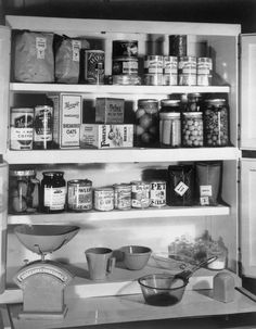 """MINISTRY OF FOOD RECOMMENDED EMERGENCY FOOD STORE FOR ONE PERSON, AUGUST 1942  part of """"MINISTRY OF FOOD SECOND WORLD WAR OFFICIAL COLLECTION"""" (photographs) Made by: Ministry of Food official photographer  An emergency larder for one person as suggested by the Ministry of Food. Included are flour, baked beans, coffee, evaporated milk and rice."""