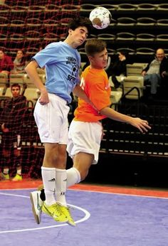 U.S. #Futsal Northeast Regional Championship  Cole Bouchard of the Jamestown team The Kure, in blue, heads the ball despite Maxwell Aunger of the Stronghold Berna Falcons, in orange, trying to stop him.