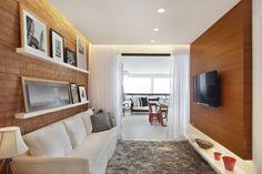 Painel de madeira, parede de tijolos prateleiras e sofá baixinho agiram para ampliar o ambiente na sala.