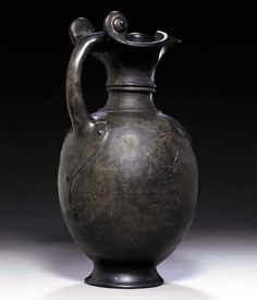 AN ETRUSCAN BUCCHERO TREFOIL OINOCHOE   Circa 6th Century B.C.   The ovoid vessel on a flaring foot, the neck with a raised ridge at the join to the body and two ridges at its center, with raised rotellae, the handle-plate leaf-shaped with three rivets in imitation of metal work  13 1/8 in. (33.3 cm) high