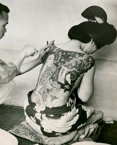 A tattoo artist traces delicate multi-colored figures on a Japanese woman,