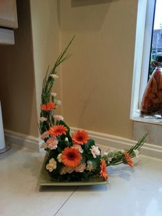 Crescent flower arrangement using germini, spray carnations and broom