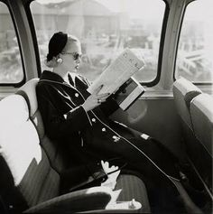 Mrs. William McManus, a Vogue fashion editor. She sits on a train, alternating her reading material between a book and a newspaper, in this portrait by Leombruno-Bodi, which appeared the April 15, 1955, Vogue. She wears a long overcoat with piped trim, a small cloche hat, and slightly oversize sunglasses. Punctuating her elegance is an intent expression, making this work not only a historic photograph but also a true study in style.