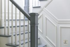 White and gray staircase boasts a gray handrail and steps as well as a white spindles.