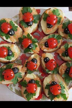 Lady bug appetizer.Cherry tomatoes and black olives make really cute lady birds. Base is made up of sliced baguettes, cream cheese, smoked salmon and flat leafed parsley. Sprinkle ground black pepper on tomato and using a toothpick dot some cream cheese on the olives for the eyes..